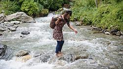 THEMENBILD - Trekkingtour in Nepal um die Annapurna Gebirgskette im Himalaya Gebirge. Das Bild wurde im Zuge einer 210 Kilometer langen Wanderung im Annapurna Gebiet zwischen 01. September 2012 und 15. September 2012 aufgenommen. im Bild durch den Monsoon werden immer wieder Straßen überflutet. Eine junge Frau versucht über Steine auf die andere Seite des Flusses zu gelangen // THEME IMAGE FEATURE - Trekking in Nepal around Annapurna massif at himalaya mountain range. The image was taken between september 1. 2012 and september 15. 2012. Picture shows a young woman try to get on the other side of the river, NEP, EXPA Pictures © 2012, PhotoCredit: EXPA/ M. Gruber