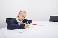 Little girl drawing on paper with felt tip pen at table