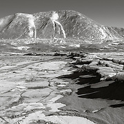 "Sand blown down Taylor Valley ends up on the sea ice. The snow figures on Mt. Coleman are know locally as ""two peeing men"". A comforting landmark I can see from Observation Hill 50 miles away at McMurdo Station."