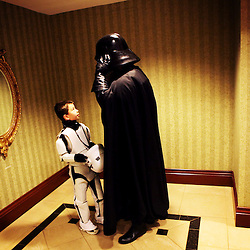 Kyle Green | The Roanoke Times<br /> 2/18/2012 Chris Atienza (right) adjusts his Darth Vader costume with the help of his son, Bennett Atienza (age 7) in a Hotel Roanoke bathroom during the SheVaCon Science Fiction, Fantasy and Horror Convention held in Roanoke, Virginia over the weekend. SheVaCon celebrated its 20th anniversary this year.
