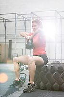 Smiling woman lifting kettlebell while sitting on tire at crossfit gym