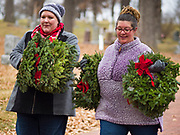14 DECEMBER 2019 - DES MOINES, IOWA: SARA CARLSON, from Des Moines, left, and STEFANIE HARPER, from Johnston, IA, carry Christmas wreaths through Woodland Cemetery. Volunteers working with Wreaths Across America placed Christmas wreaths on the headstones of more than 600 US military veterans in Woodland Cemetery in Des Moines. The cemetery, one of the first in Des Moines, has the graves of veterans going back to the War of 1812.     PHOTO BY JACK KURTZ