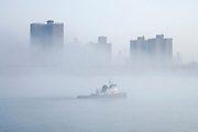 tugboat in fog on the East River in NYC