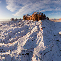 USA, Arizona, Monument Valley Navajo Tribal Park, Aerial panoramic view of sunrise lighting Monument Valley in snow on winter morning