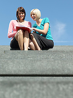 Two women sitting on stairs outdoors reading papers and laughing low angle view
