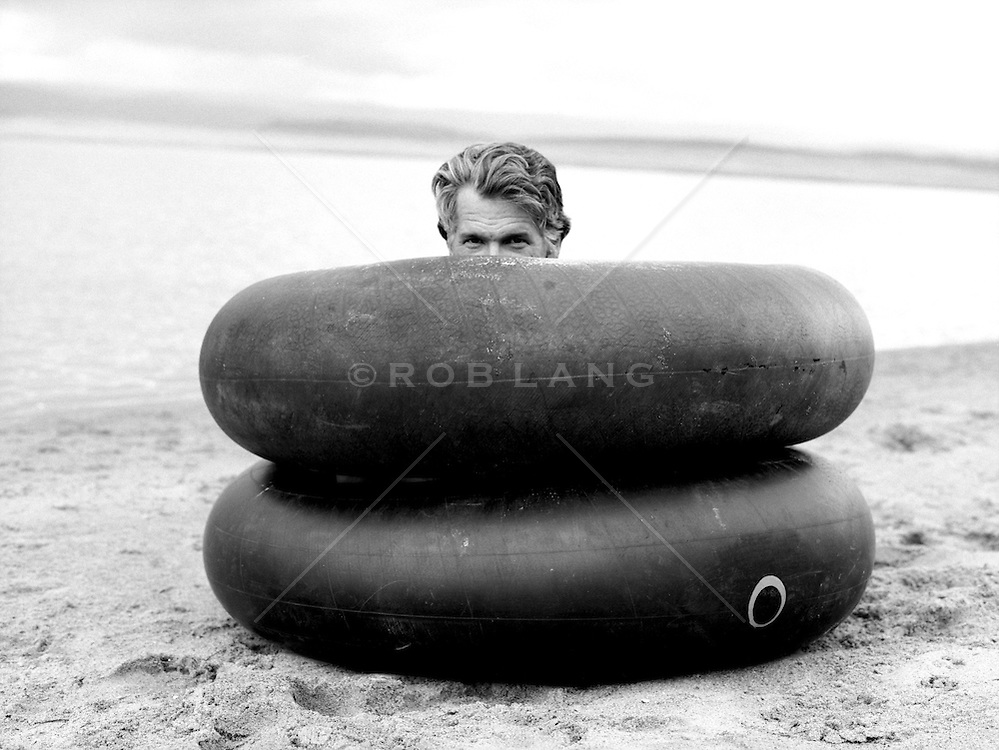 man peering out from two inner tubes on the beach