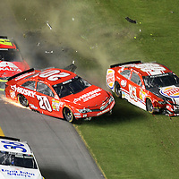NASCAR Sprint Cup drivers Matt Kenseth (20), Jeff Gordon (24) and  David Reutimann (83) wreck during the NASCAR Coke Zero 400 Sprint series auto race at the Daytona International Speedway on Saturday, July 6, 2013 in Daytona Beach, Florida.  (AP Photo/Alex Menendez)
