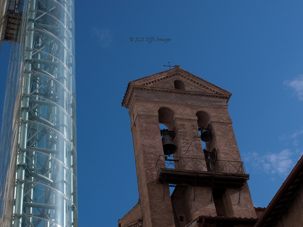 Glass exterior elevator on the Vittorio Emanuele and the bell tower of Santa Maria in Aracoeli, against a clear blue sky.  A stark contrast of a contemporary structure adjoining a Romanesque one.