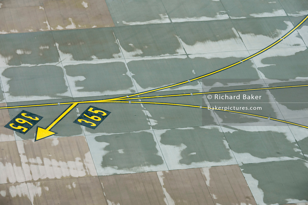 High aerial view (from control tower) of Heathrow airport aviation markings on concrete landscape.