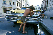 Little kid cleaning the lights of a yellow Dodge car, Cuba