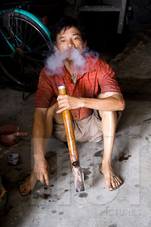 Man smoking typical vietnamese water pipe composed of a bamboo and a bonfire