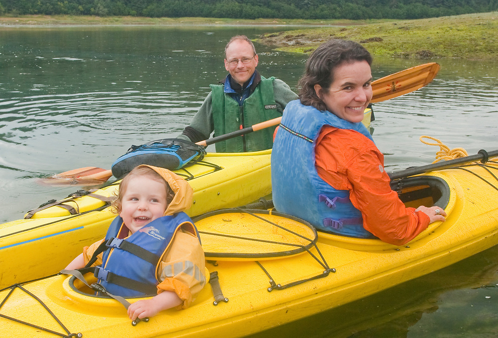 A happy family paddling yellow kayaks in Glacier Bay National Park. MR MRA
