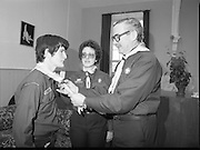 Scout Inducted Using Sign Language.   (P6)..1981..08.12.1981..12.08.1981..8th December 1981..Joe Needham, a deaf and dumb resident in Stewart's Hospital, Palmerstown, Co Dublin was enrolled into the 43rd Dublin (Palmerstown) unit of the Scouting Association of Ireland. The Chief Scout, Mr Joe McGough carried out the enrollment at the hospital. Ms Domenica Malocca, a teacher in the class for the deaf at the hospital, translated the Scout Promise into sign language during the ceremony...Picture taken of Joe Needham being officially welcomed into the Irish Scouting Movement by the Chief Scout, Mr Joe McGough and Estelle Feldman, Scout Leader, 43rd Dublin Unit, Palmerstown.