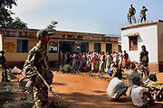 In the village of Pandewar police and special security stand guard whilst villagers cast their vote for the second time in the state elections. Voting a few weeks before in the same village had resulted in the Naxalites destroying the (EVM) electronic voting machine and threatening locals that their hands would be chopped off if they voted again.