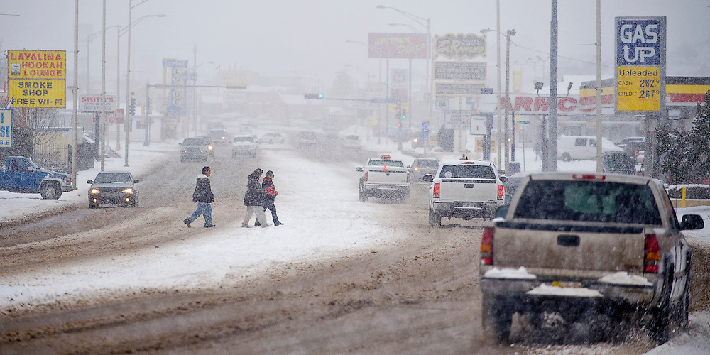 012110        Brian Leddy.Pedestrians cross Historic Route 66 as snow falls and traffic flows on Thursday morning. Approximately two to four inches of snow hit the area with plenty more on the way.