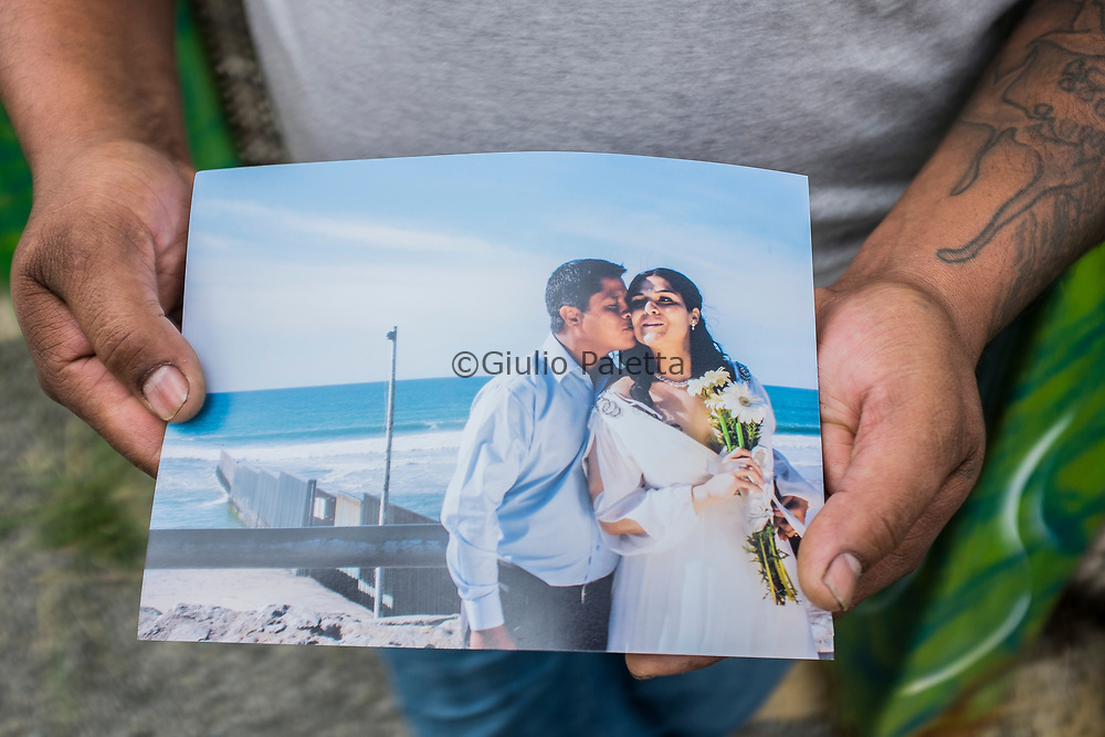 """Hugo Velasco, 45 years. He used to live with his wife in Chicago. In 2012 He was deported and sine then He moved to Tijuana in order to stay closer to her wife who comes to visit him in Tijuana once a year. Here showing the picture of their wedding, right in front of the wall in Tijuana, in 2013. Every Sundays, deported Mexicans meet with their relatives on the other side of the border through the infamous """"wall"""". American border guards open the internal gates of the International Frienship park for 4 hours to allow relatives who are on the American side of the border to see and speak to each others. They can't touch each others though, but at least for those 4 hours they will feel closer."""