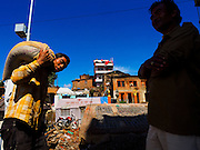 03 AUGUST 2015 - SANKHU, NEPAL: People walk past a Hindu temple destroyed in the Nepal earthquake in Sankhu, a community about 90 minutes from central Kathmandu. The Nepal Earthquake on April 25, 2015, (also known as the Gorkha earthquake) killed more than 9,000 people and injured more than 23,000. It had a magnitude of 7.8. The epicenter was east of the district of Lamjung, and its hypocenter was at a depth of approximately 15km (9.3mi). It was the worst natural disaster to strike Nepal since the 1934 Nepal–Bihar earthquake. The earthquake triggered an avalanche on Mount Everest, killing at least 19. The earthquake also set off an avalanche in the Langtang valley, where 250 people were reported missing. Hundreds of thousands of people were made homeless with entire villages flattened across many districts of the country. Centuries-old buildings were destroyed at UNESCO World Heritage sites in the Kathmandu Valley, including some at the Kathmandu Durbar Square, the Patan Durbar Squar, the Bhaktapur Durbar Square, the Changu Narayan Temple and the Swayambhunath Stupa. Geophysicists and other experts had warned for decades that Nepal was vulnerable to a deadly earthquake, particularly because of its geology, urbanization, and architecture.    PHOTO BY JACK KURTZ