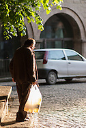 An old man slowly walking home at the sunset in Viterbo, Lazio, Italy.