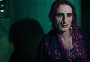 Reema, a 35 year old Hijra prepares arrives at the apartment of Sheza Shahnawaz prior to leaving for the evenings work on the streets of Karachi...The word Hijra is an Urdu word meaning eunuch or hermaphrodite. However, most Hijras in Pakistan are gay men who leave home to join the Hijra community as young boys where there is more acceptance. Most identify themselves as more feminine then masculine and dress and act accordingly...Although tolerated in a country where homosexuality is against the law, Hijras are largely ostracised from society. They are often denied work opportunities, rejected by most families, lack formal education and live in poorer areas of the city...They share similarities with the more famous Hijra communities in the Indian subcontinent and Bangladesh. In a continent where great emphasis is placed on one's ability to have children, those who are unfortunate not to be able to conceive children are not considered a true man or woman. Life for many Hijras in Pakistan consists of begging for alms (Zakat) in the more prosperous areas of the city as well as slums in addition to receiving alms when bestowing blessings on male babies and at weddings....Most Hijras dress as women, and engage in activities such as dancing and entertaining in public - activities that would be considered inappropriate for women of the subcontinent. Some members of the community engage in prostitution. .