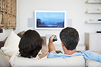 Couple using remote control sitting in front of television in living room back view
