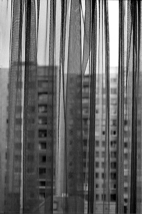 .A view of housing through curtains. Old apartments are being painted to inflate prices and attract first time buyers. From neighborhoods series.**Neighborhoods