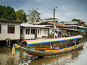 27 JUNE 2015 - BANGKOK, THAILAND:   A boat on Khlong Bang Luang in the Bang Luang neighborhood of the Thonburi section of Bangkok. The Bang Luang neighborhood lines Khlong (Canal) Bang Luang in the Thonburi section of Bangkok on the west side of Chao Phraya River. It was established in the late 18th Century by King Taksin the Great after the Burmese sacked the Siamese capital of Ayutthaya. The neighborhood, like most of Thonburi, is relatively undeveloped and still criss crossed by the canals which once made Bangkok famous. It's now a popular day trip from central Bangkok and offers a glimpse into what the city used to be like.       PHOTO BY JACK KURTZ