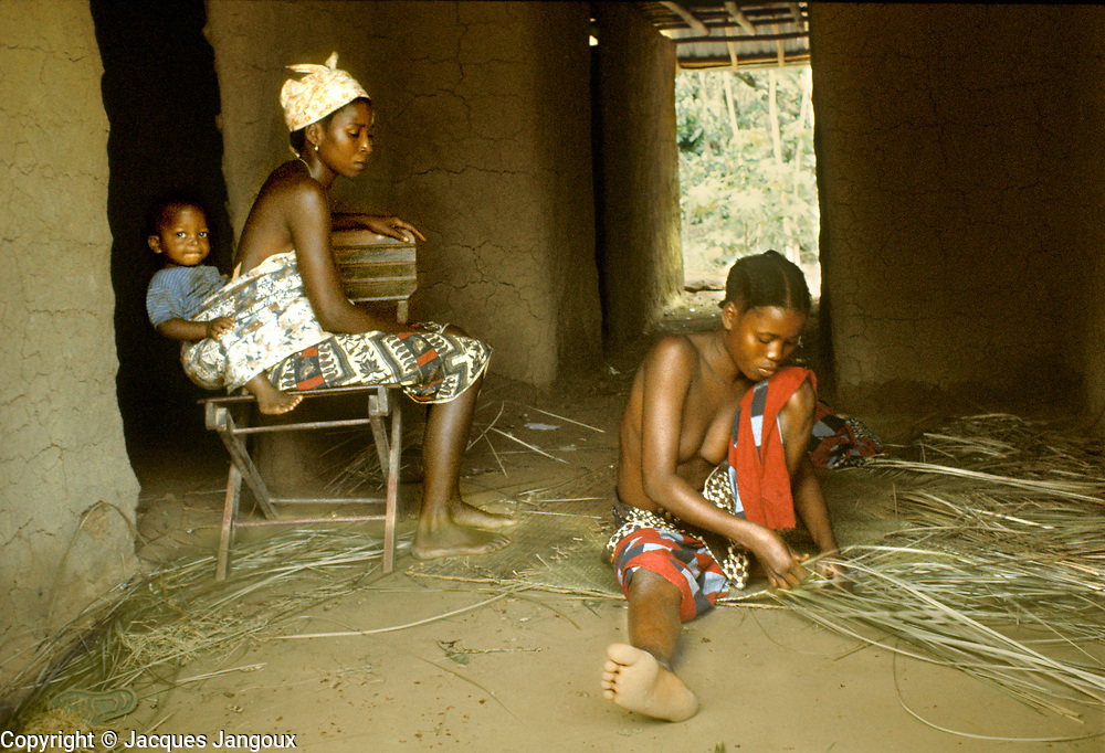 village life in Africa: Women of Kpelle (Guerze) tribe socializing inside hut, young one at right weaving mat, woman at left carrying baby strapped on her back, Liberia, West Africa.