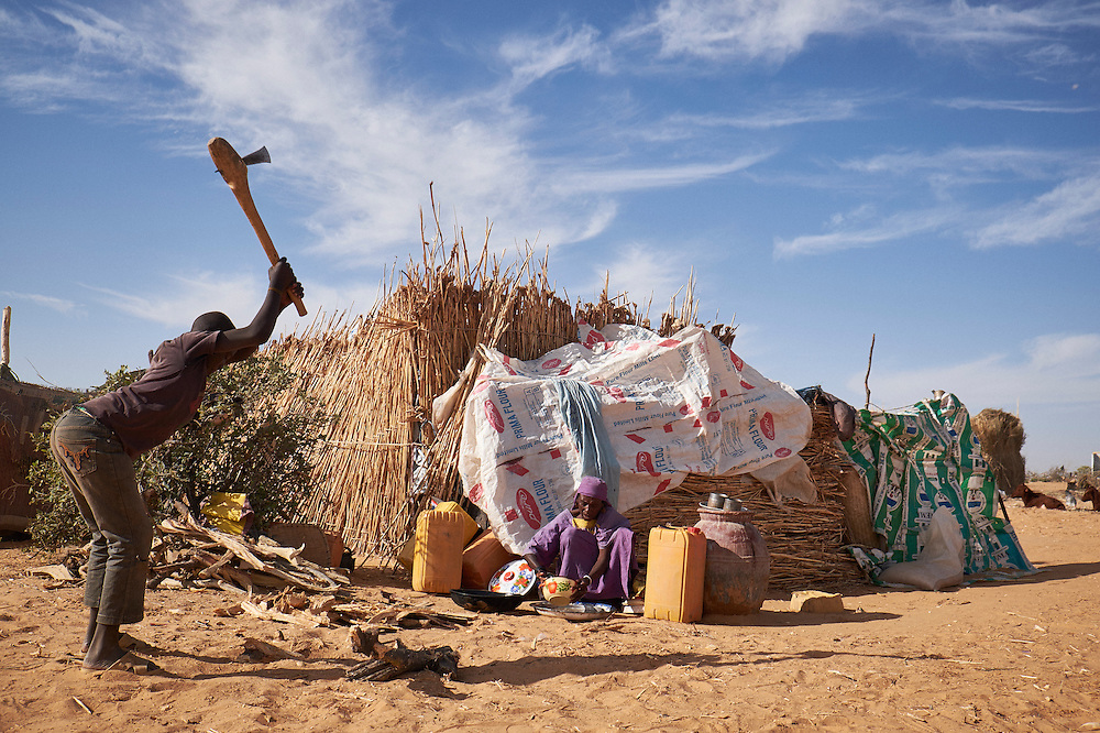 A boy cuts wood as a woman prepares a meal at a camp of internally displaced people near the village of Kouble by the side of the road on the highway outside of Diffa, Niger on February 17, 2016. The camp is made up of displaced people and refugees from villages along the border between Niger and Nigeria and who fled attacks from Boko Haram.