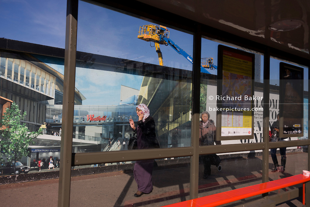 Muslim lady passes a hoarding showing aspiration and consumerism of nearby Westfield City shopping complex, Stratford