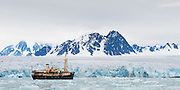 Expedition ship MS Origo anchored next to a glacier