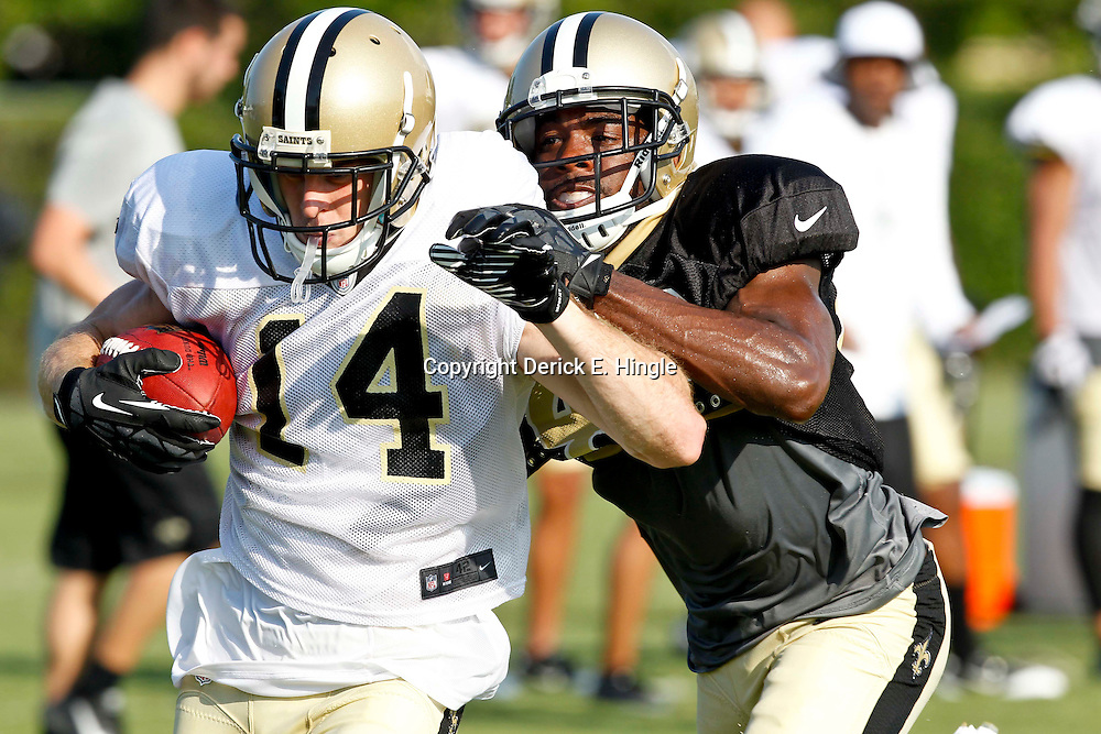 July 29, 2012; Metairie, LA, USA; New Orleans Saints wide receiver Andy Tanner (14) catches a pass over safety Isa Abdul-Quddus (42) during a training camp practice at the team's practice facility. Mandatory Credit: Derick E. Hingle-US PRESSWIRE