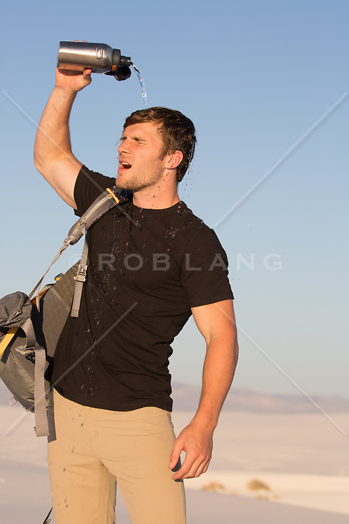 hiker pouring water over his head in the desert