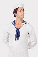 Thoughtful young man in sailor's uniform looking away against gray background