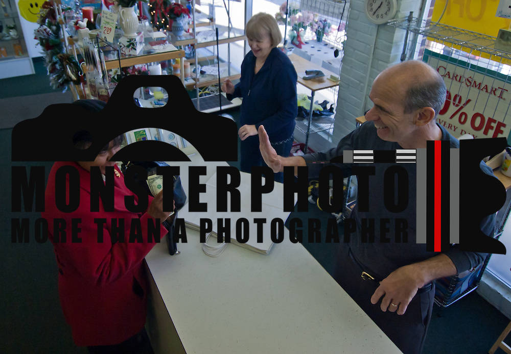12/24/10 New Castle DE: Crown Gifts owner Gus and his wife Barbara Coccia helping customers Caroline Permell (Left) at his card shop in New Castle Delaware. Crown Gifts is closing it's doors after 35 years because of the recession...Special to The News Journal/SAQUAN STIMPSON