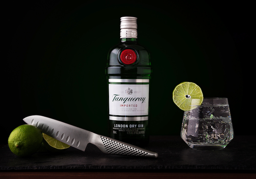 A studio beverage photo for Tanqueray London Dry Gin. Each element of the photo, from the glassware to the knife and the wood and stone base, where styled to suit the bottle.