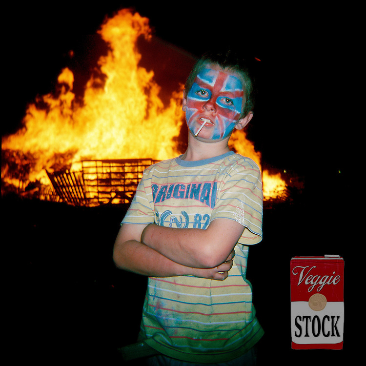 A child painted with the union jack poses for a photo next to a bonfire in Belfast, Northern Ireland, July 2008.<br /> The bonfires are built in preparation for the annual 12th July celebrations, which commemorate the defeat of James Stuart at the Battle of the Boyne in 1690.<br /> credit: Megan Young