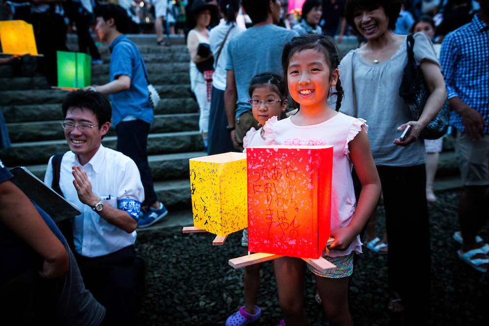 HIROSHIMA, JAPAN - AUGUST 6 : Children wait to float candle lit lantern with their written message on the Motoyasu River during the 71st anniversary activities, commemorating the atomic bombing of Hiroshima at the Hiroshima Peace Memorial Park on August 6, 2016 in Hiroshima, western Japan. Japan marks the 71st anniversary of the first atomic bomb that was dropped by the United States on Hiroshima on August 6, 1945 during World War II.  (Photo by Richard Atrero de Guzman/NURPhoto)