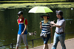 © Licensed to London News Pictures. 07/08/2018. London, UK.  Tourists walk with an umbrella through St James's Park in London during another day of hot and sunny weather in the capital.  Photo credit: Vickie Flores/LNP
