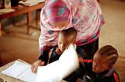Een lerares geeft op vrijwillige basis onderwijs aan kinderen van arme afkomst.