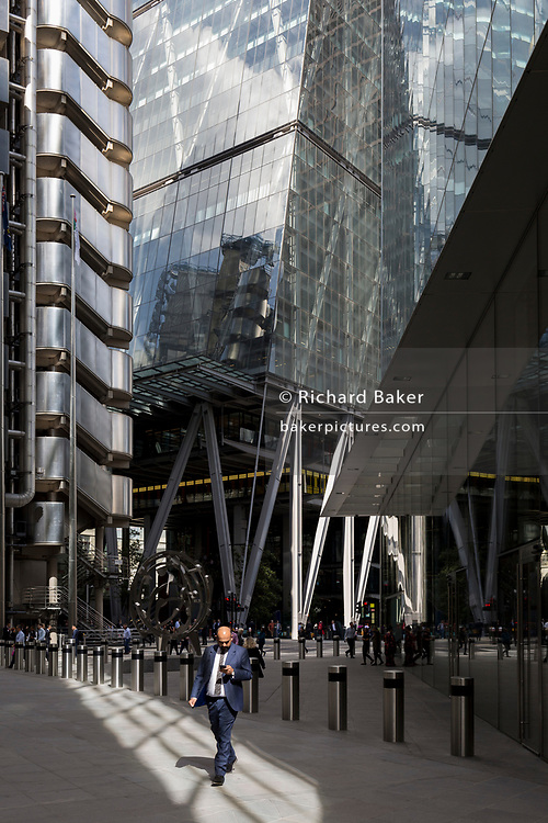 City workers walk through the modern architecture of Lloyds of London (left) and the Leadenhall Building (right) in the City of London, (aka The Square Mile) the capital's financial district, on 2nd September 2019, in London, England.