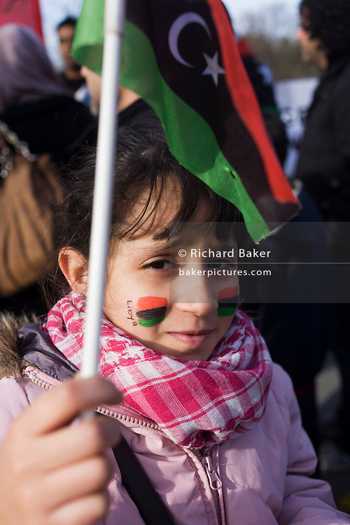 Young girl holds the flag of the independent kingdom as Libyan exiles protest outside their London embassy...The flag of the independent kingdom was red, black, and green with a crescent and star in the center. After the Libyan revolution of 1969, the flag was changed to the Arab Liberation Flag of horizontal red, white, and black bands. In 1971 Libya joined the Federation of Arab Republics with Egypt and Syria, which used a similar flag with a hawk emblem in the center and the name of the country beneath it. When Libya left the Federation in 1977, the new plain green flag was adopted. But during the 2011 uprising, the old flag was once again adopted.