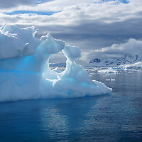 A blue iceberg which looks as though a window was sculpted into it.  The photograph was taken in Antarctica.