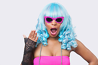 Portrait of surprised African American woman in blue wig over white background