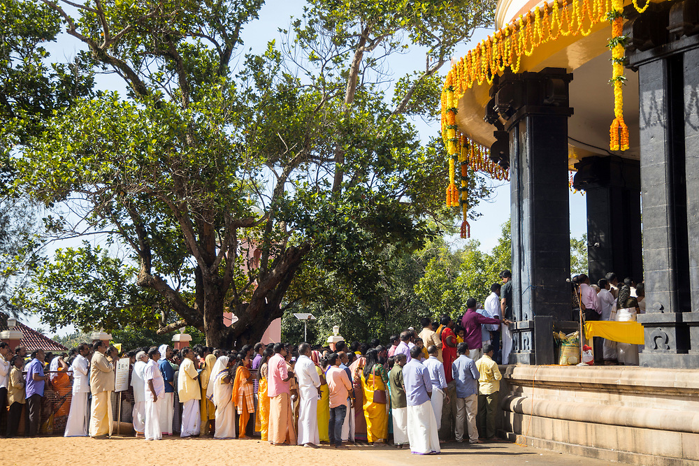 "VARKALA, INDIA - 21st September 2019 - Pilgrims and Hindu holy men perform a puja prayer ritual for Sree Narayana Guru during his memorial day at the Sivagiri Mutt pilgrimage centre. Sree Narayana Guru was a spiritual leader who led a reform movement against the injustice of the caste system in India. He promoted the term ""One Caste, One Religion, One God for All."" The Sivagiri Mutt is the believed site of the guru's enlightenment and is now home to the headquarters of the Sree Narayana Dharma Sangham - an organisation built by his disciples and followers. Kerala, Southern India."