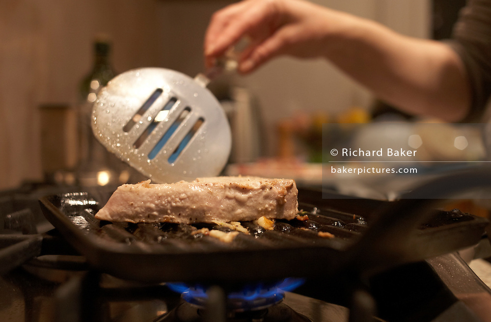 Fresh Maldives line caught yellow fin tuna steaks are grilled in heavy pan on a Friday night in a London kitchen