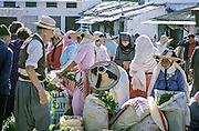 AFRICA, MOROCCO, TANGIER:  Berber women in traditional dress selling vegetables and herbs at an open air market in old Tangier.