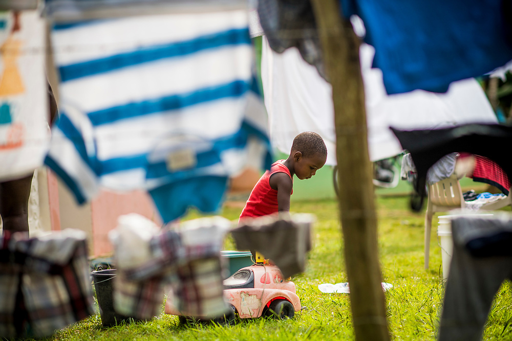 July 21, 2017, Boston, MA:<br /> A local boy is seen walking through a fence full of laundry in El Mam&oacute;n during the 2017 Lindos Sue&ntilde;os trip in the Dominican Republic Friday, July 21, 2017. <br /> (Photo by Billie Weiss/Boston Red Sox)