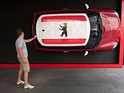 Mini motor car on wall outside Mini showroom store on Friedrichstrasse in Berlin Germany