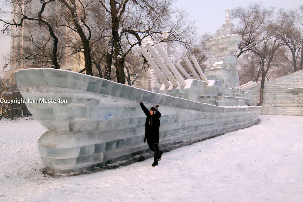 Visitor looking at battleship carved from ice at the annual Harbin ice sculpture festival in northern China