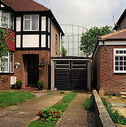 Victorian gasometer behind London suburban homes. 2003